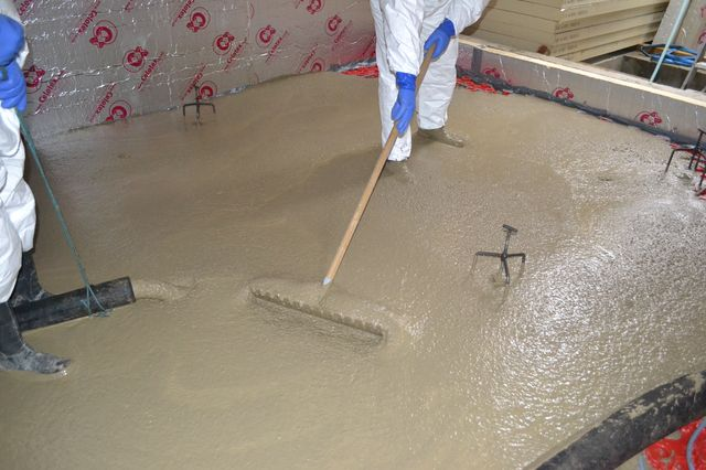 Thermotech operatives placing structural screed in basement